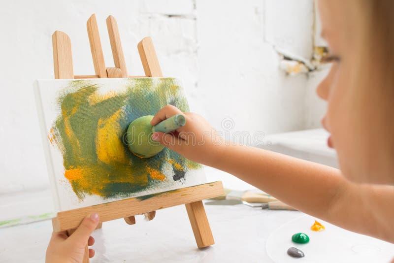 Λίγος δημιουργικός ζωγράφος στη διαδικασία εργασίας στοκ εικόνες