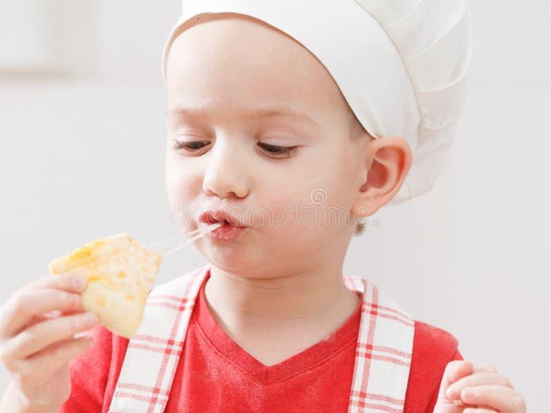 Λίγος εύθυμος αρχιμάγειρας αγοριών μαγειρεύει και τρώει την πίτσα στοκ φωτογραφία