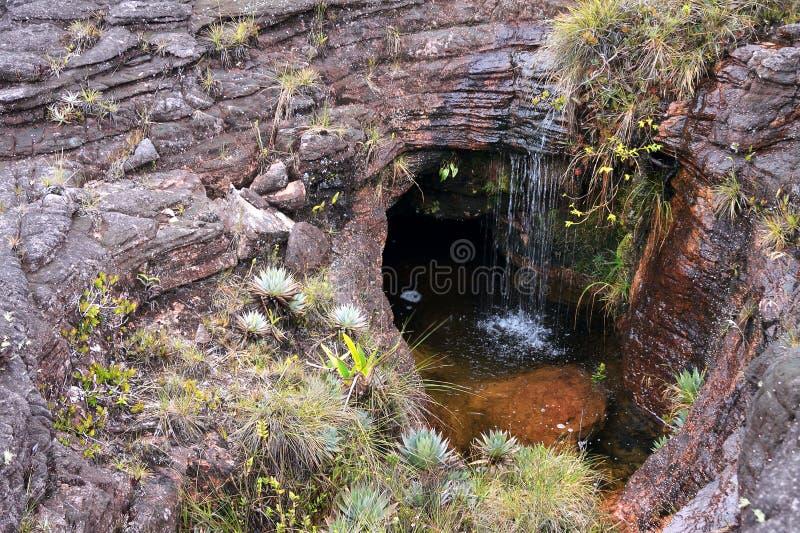 Λίγος καταρράκτης στην τρύπα αποχέτευσης μέσα στο βράχο στο υποστήριγμα Roraima στοκ εικόνες