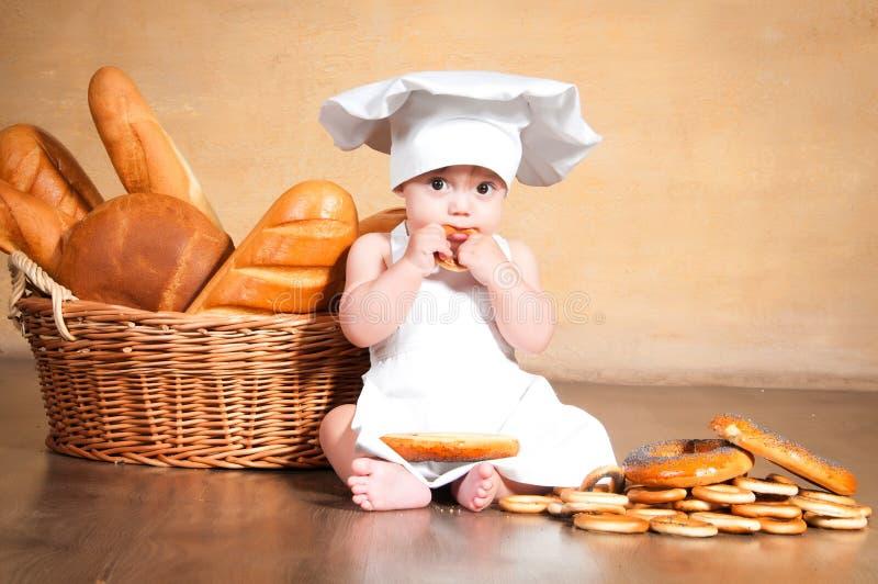 Λίγος μάγειρας με bagel στα χέρια της στοκ φωτογραφία
