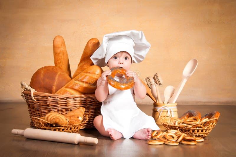 Λίγος μάγειρας με bagel στα χέρια της στοκ εικόνες