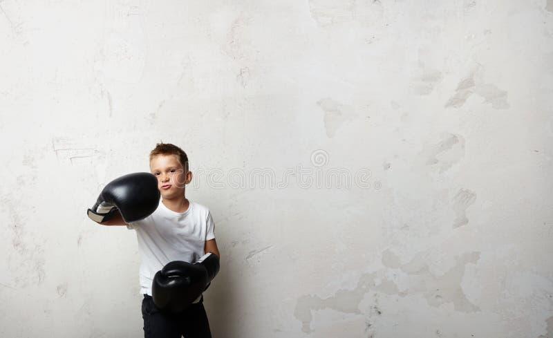 Λίγος μαχητής μπόξερ που στέκεται στα εγκιβωτίζοντας γάντια και στοκ εικόνα με δικαίωμα ελεύθερης χρήσης