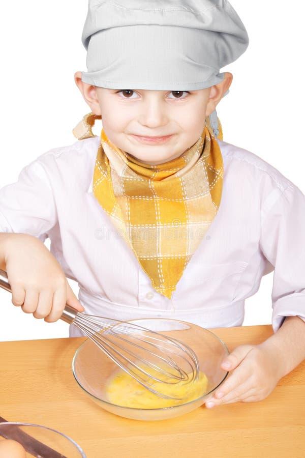 Λίγος χαμογελώντας μάγειρας που χτυπά ελαφρά τα αυγά σε ένα κύπελλο στοκ φωτογραφίες