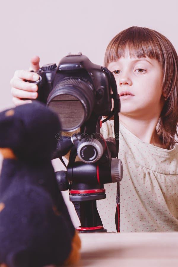 Λίγος χαριτωμένος φωτογράφος κοριτσιών παιδιών παίρνει το πορτρέτο του σκυλιού παιχνιδιών με μια κάμερα DSLR στοκ εικόνες με δικαίωμα ελεύθερης χρήσης