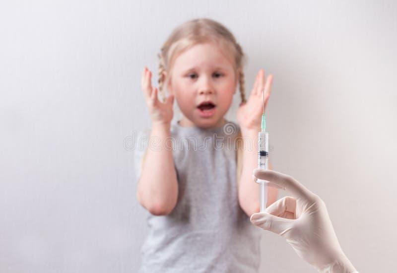 Λίγος χαριτωμένος φόβος κοριτσιών της έγχυσης Εμβολιασμός των παιδιών στοκ φωτογραφίες