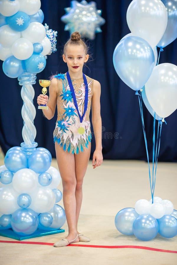 Λίγος gymnast με τα αθλητικά βραβεία της στον τάπητα στη ρυθμική γυμναστική στοκ φωτογραφία με δικαίωμα ελεύθερης χρήσης