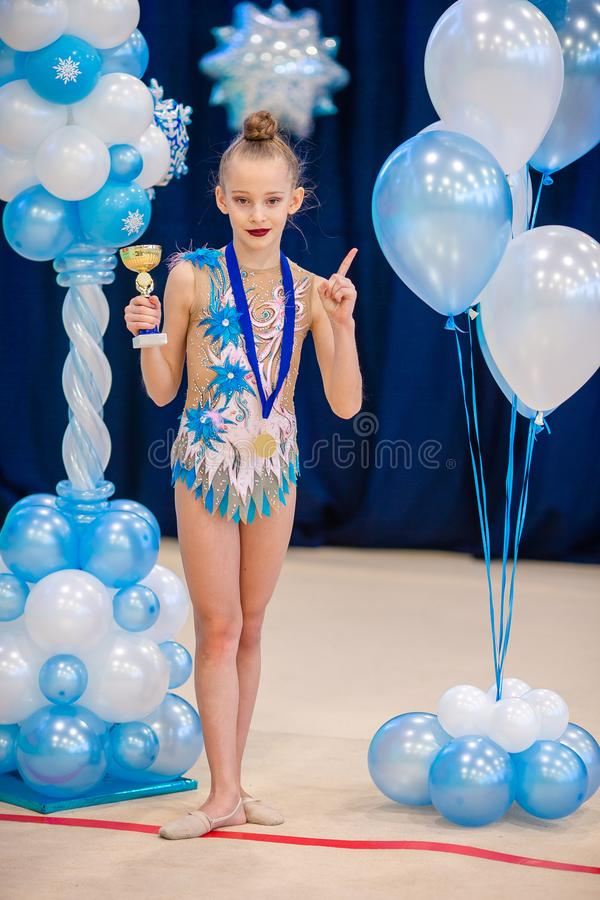 Λίγος gymnast με τα αθλητικά βραβεία της στον τάπητα στη ρυθμική γυμναστική στοκ εικόνα