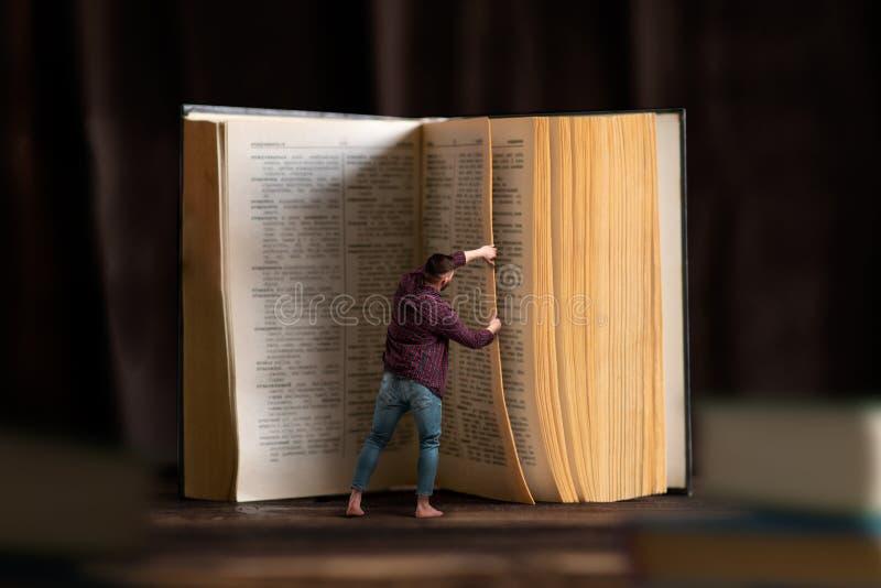 Λίγο άτομο γυρίζει τη σελίδα του μεγάλου βιβλίου, ανάγνωση στοκ εικόνες με δικαίωμα ελεύθερης χρήσης