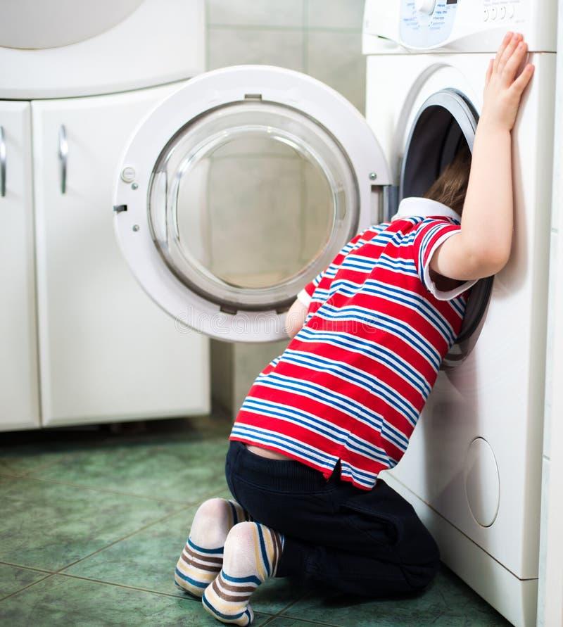 Λίγο αγοράκι που βάζει επικίνδυνα το κεφάλι του στο τύμπανο πλυντηρίων στοκ φωτογραφίες με δικαίωμα ελεύθερης χρήσης