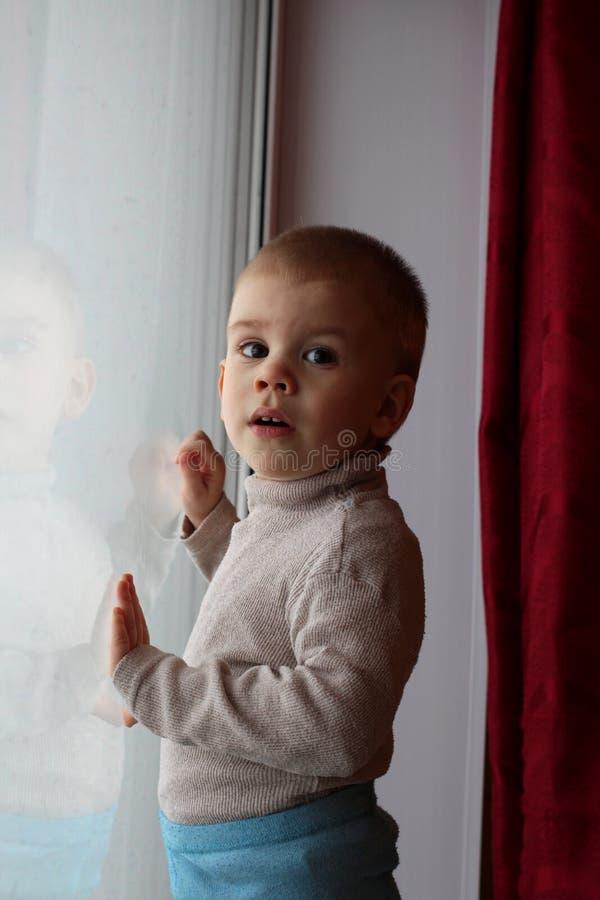 Λίγο αγοράκι που στέκεται στο windowsill που φαίνεται έξω το παράθυρο στοκ εικόνα με δικαίωμα ελεύθερης χρήσης