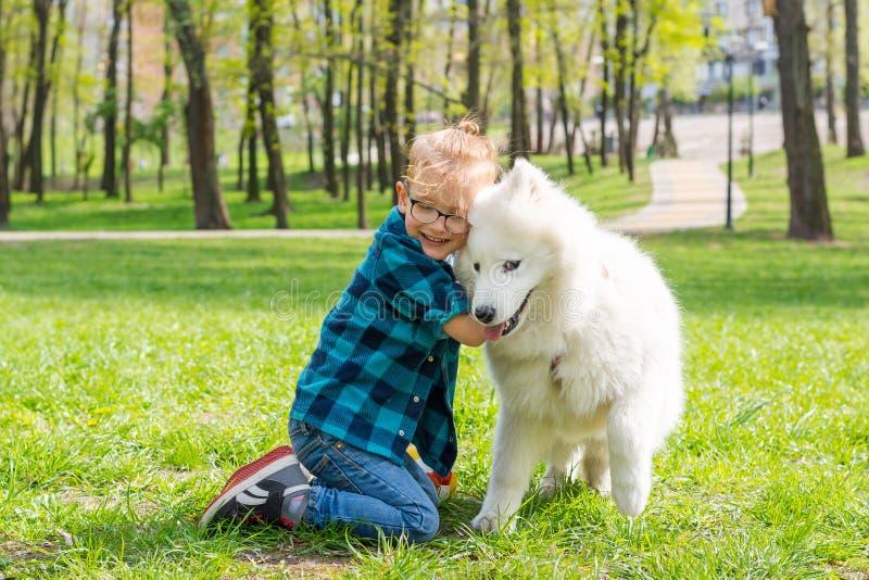 Λίγο αγόρι hipster στα γυαλιά που αγκαλιάζει άσπρο χνουδωτό το σκυλί και το γέλιο στο πάρκο στη χλόη στοκ εικόνες