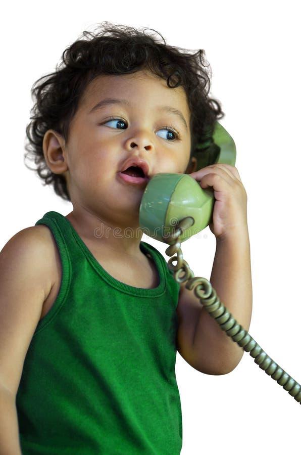 Λίγο ασιατικό αγοράκι που μιλά σε ένα αναδρομικό τηλέφωνο στοκ εικόνες