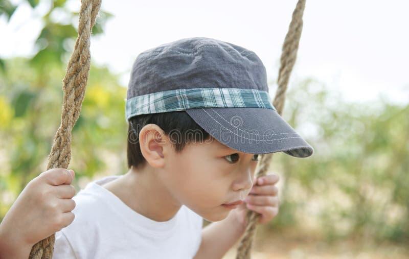 Λίγο ασιατικό αγόρι που κοιτάζει και που παίζει στην ταλάντευση: Κλείστε επάνω στοκ εικόνα με δικαίωμα ελεύθερης χρήσης