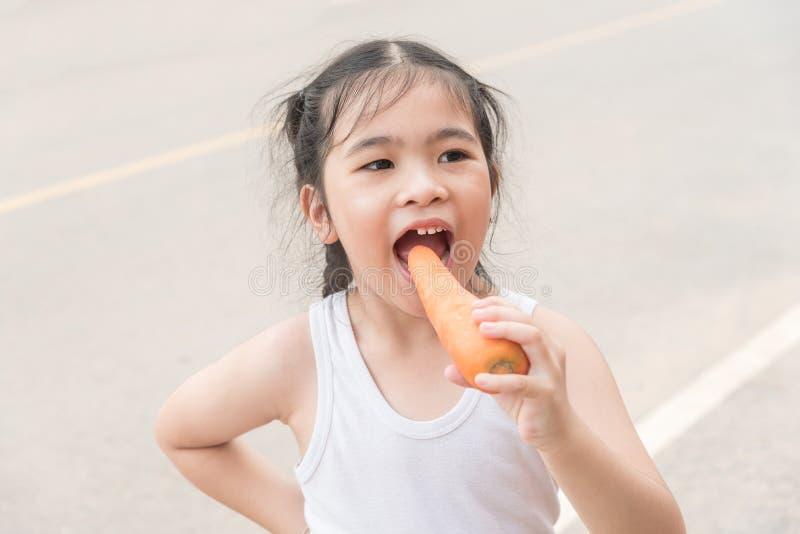 Λίγο ασιατικό κορίτσι απολαμβάνει τρώει ένα καρότο Στο δρόμο στοκ εικόνα
