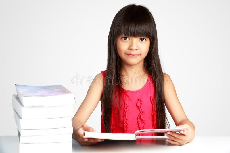 Λίγο ασιατικό κορίτσι με τα βιβλία στον πίνακα στοκ εικόνα με δικαίωμα ελεύθερης χρήσης