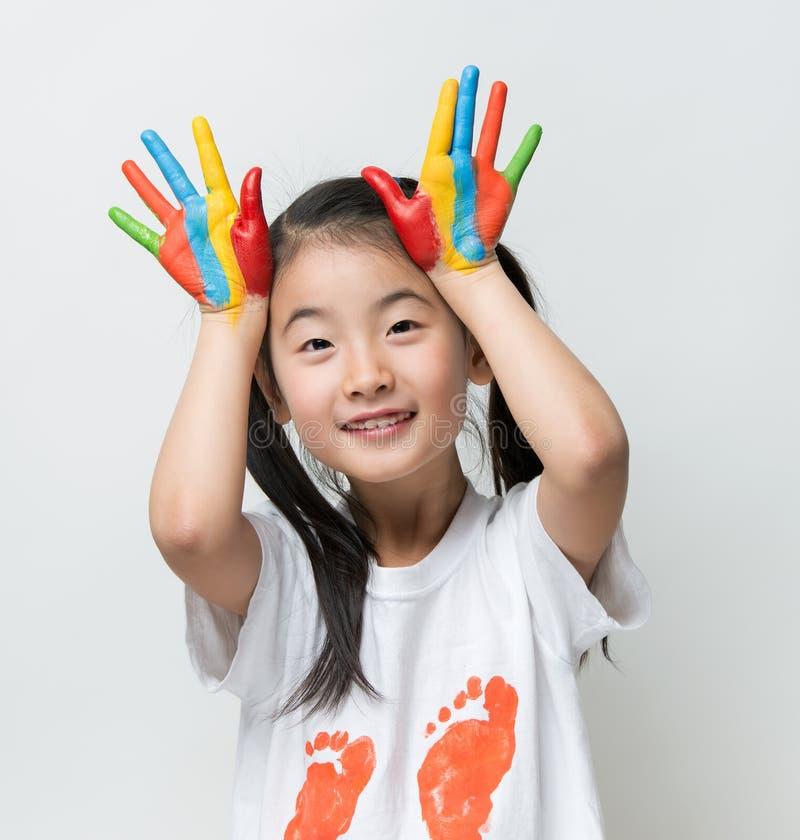 Λίγο ασιατικό κορίτσι με τα χέρια χρωμάτισε στα ζωηρόχρωμα χρώματα στοκ φωτογραφίες