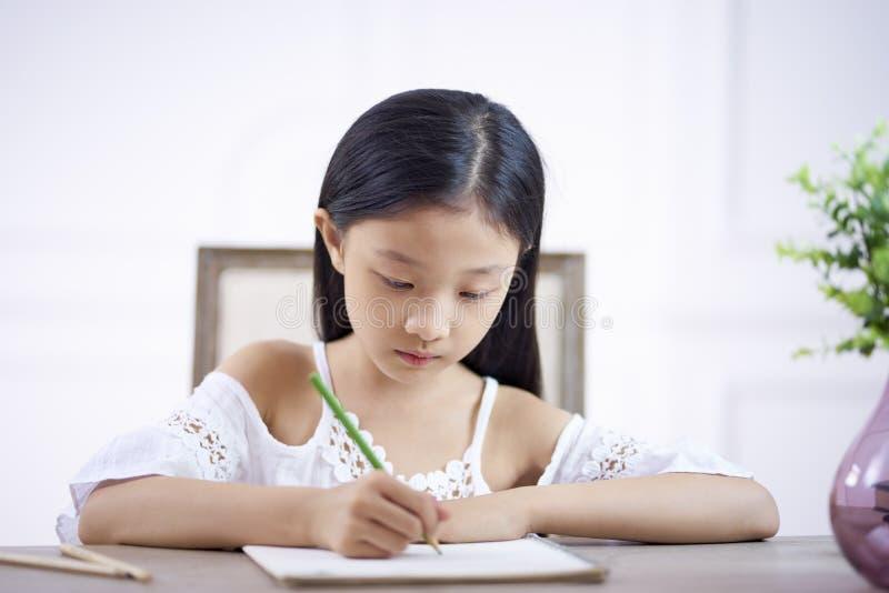 Λίγο ασιατικό κορίτσι που γράφει ή που σύρει στοκ εικόνα