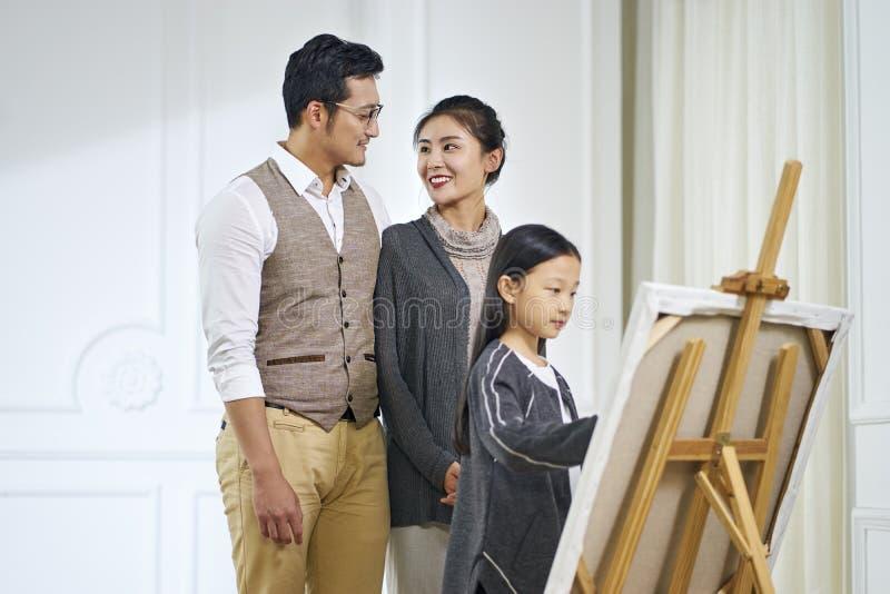 Λίγο ασιατικό κορίτσι που κάνει μια ζωγραφική με την προσοχή γονέων στοκ εικόνες με δικαίωμα ελεύθερης χρήσης