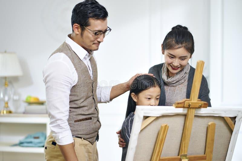Λίγο ασιατικό κορίτσι που κάνει μια ζωγραφική με τους γονείς που προσέχουν και που βοηθούν στοκ φωτογραφία με δικαίωμα ελεύθερης χρήσης