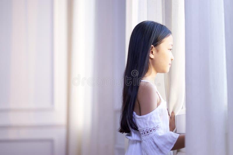 Λίγο ασιατικό κορίτσι που κοιτάζει από το παράθυρο στοκ εικόνα