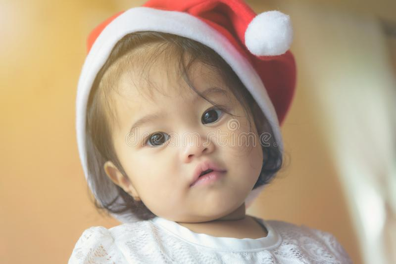 Λίγο ασιατικό κορίτσι που φορά ένα διαγώνιο καπέλο Santa Έχει έναν χαριτωμένο και ένα inno στοκ φωτογραφίες με δικαίωμα ελεύθερης χρήσης