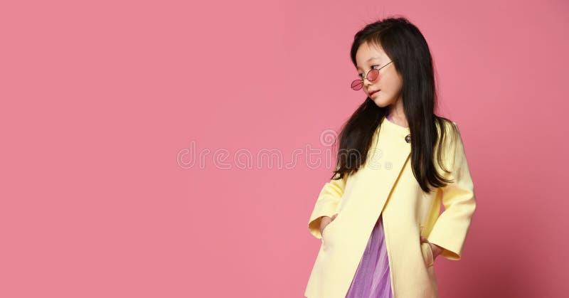 Λίγο ασιατικό κορίτσι στο κίτρινο πορφυρό φόρεμα σακακιών μόδας και τη σύγχρονη κόκκινη τοποθέτηση γυαλιών ηλίου στοκ φωτογραφίες