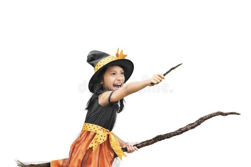 Λίγο ασιατικό κορίτσι στο κοστούμι μαγισσών που χρησιμοποιεί τη μαγικές ράβδο και τη σκούπα στοκ φωτογραφία με δικαίωμα ελεύθερης χρήσης