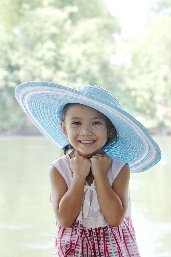 Λίγο ασιατικό κορίτσι υπαίθρια στο θερινό καπέλο στοκ εικόνες
