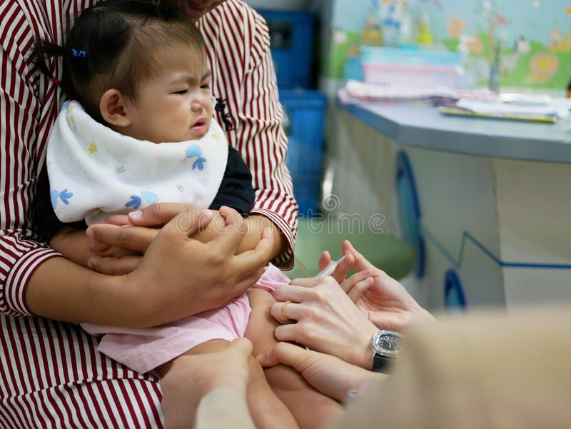 Λίγο ασιατικό κοριτσάκι, ενός έτους βρέφος, στον πόνο ενώ παιδιατρικές νοσοκόμες που εξασφαλίζουν το πόδι της και που δίνουν της  στοκ εικόνες με δικαίωμα ελεύθερης χρήσης