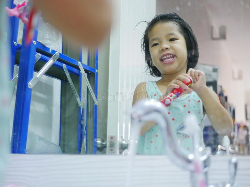 Λίγο ασιατικό κοριτσάκι που για να ανοίξει μια οδοντόπαστα ΚΑΠ μπροστά από έναν καθρέφτη από μόνη της στοκ εικόνα με δικαίωμα ελεύθερης χρήσης