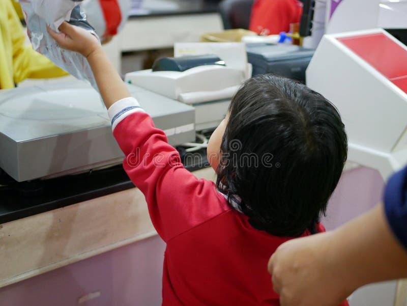 Λίγο ασιατικό κοριτσάκι που δίνει το δέμα της μητέρας της σε ένα προσωπικό ταχυδρομείων για να ζυγίσει και να υπολογίσει την αξία στοκ φωτογραφία με δικαίωμα ελεύθερης χρήσης