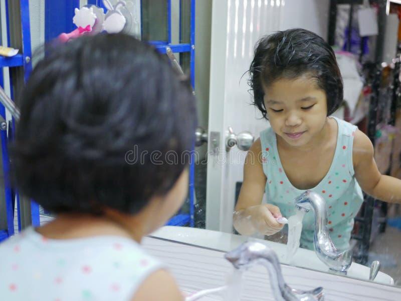 Λίγο ασιατικό κοριτσάκι που πλένει την οδοντόβουρτσά της μπροστά από έναν καθρέφτη από μόνη της στοκ εικόνες