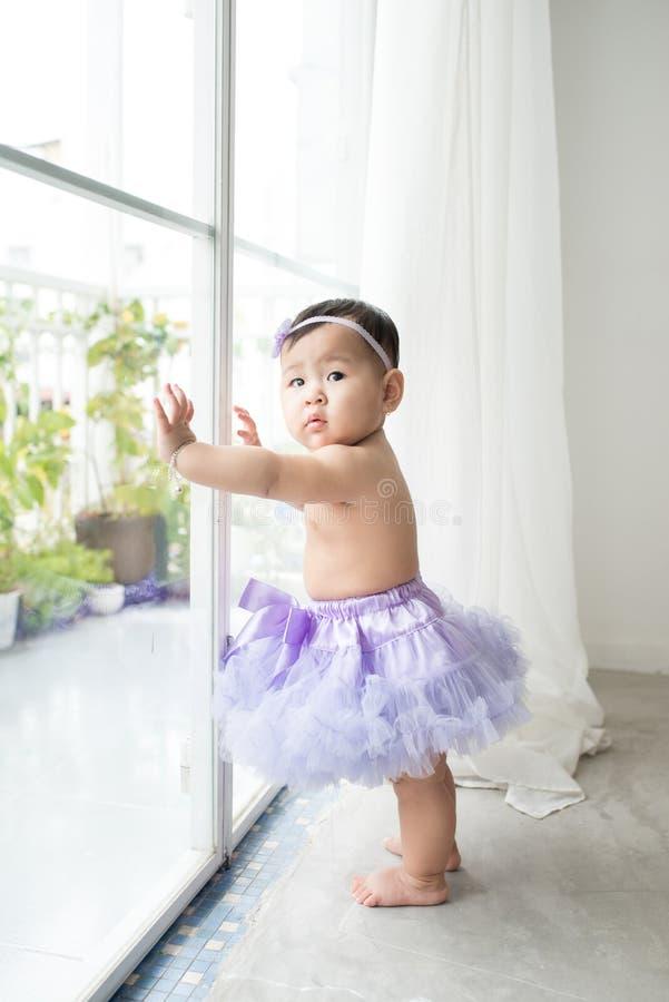 Λίγο ασιατικό κοριτσάκι στο σπίτι στο άσπρο δωμάτιο στέκεται κοντά στο παράθυρο στοκ εικόνα με δικαίωμα ελεύθερης χρήσης