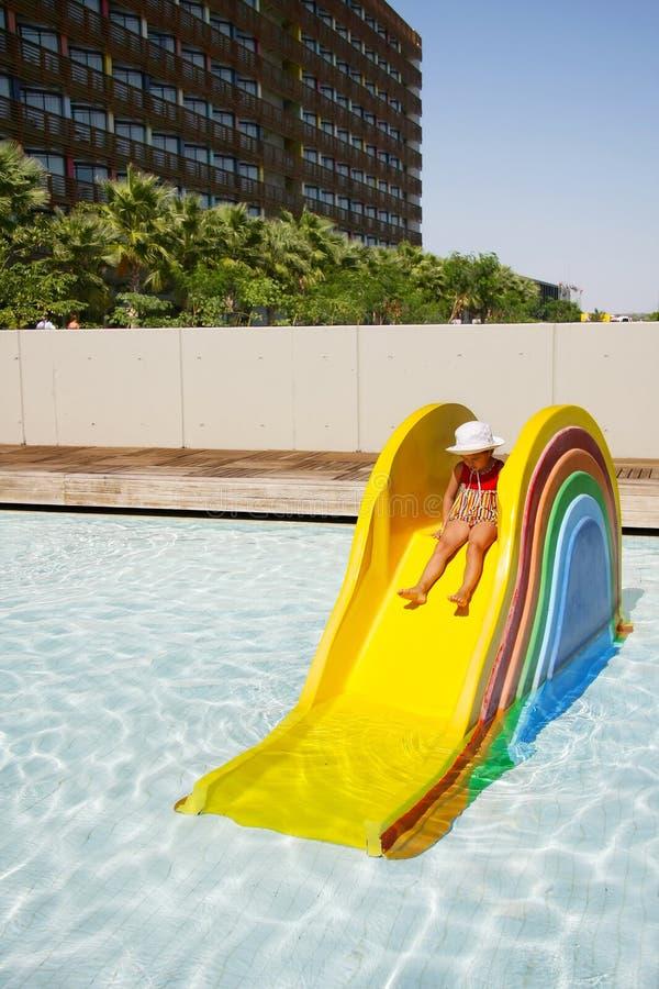 Λίγο αστείο κορίτσι σε ένα ζωηρόχρωμο μίνι waterslide στη φωτεινή λίμνη στοκ φωτογραφίες