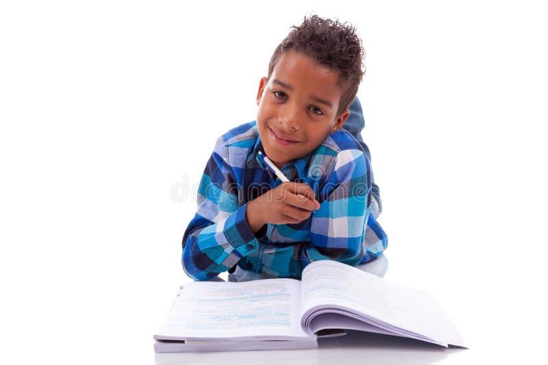 Λίγο αφρικανικό αγόρι που ξαπλώνει στο πάτωμα και που διαβάζει το βιβλίο στοκ φωτογραφία με δικαίωμα ελεύθερης χρήσης