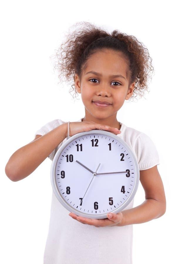 Λίγο αφρικανικό ασιατικό κορίτσι που κρατά ένα ρολόι στοκ εικόνα