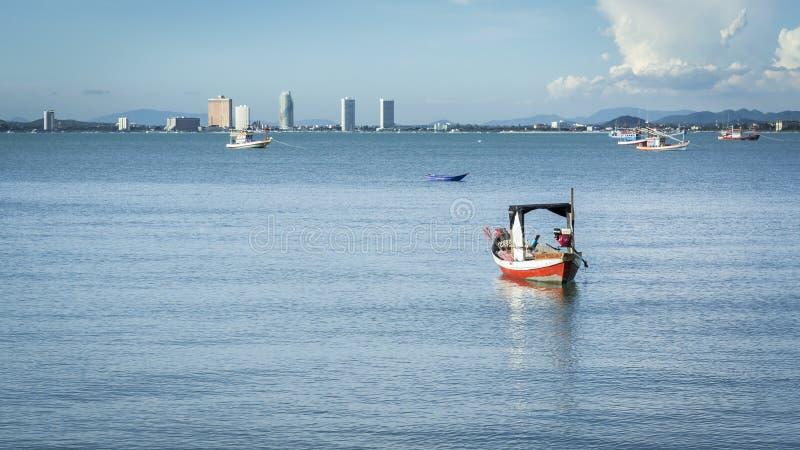 Λίγο αλιευτικό σκάφος στο νερό στην παραλία με το μπλε ουρανό και πόλη στο υπόβαθρο στοκ φωτογραφία με δικαίωμα ελεύθερης χρήσης