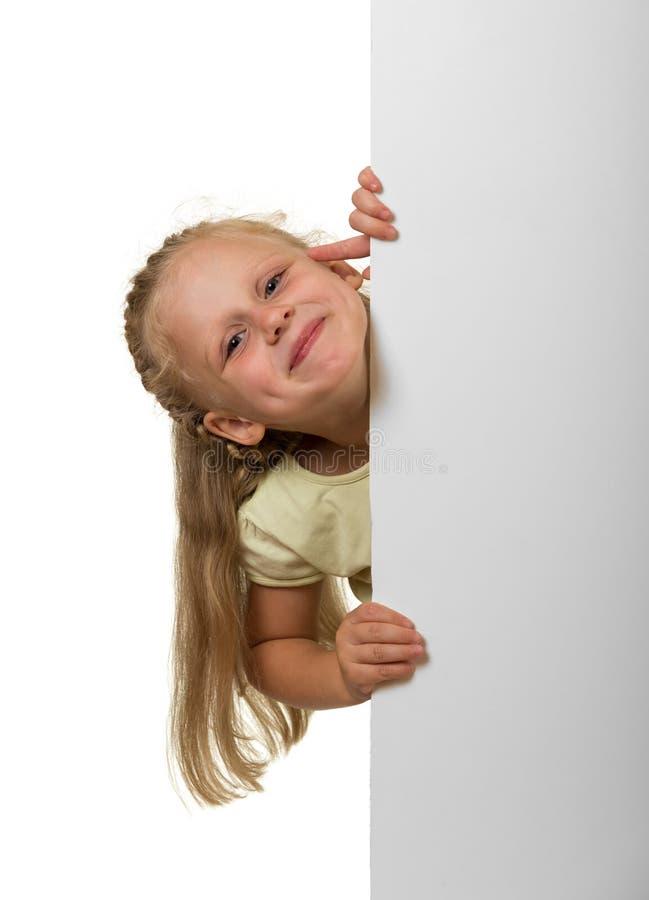 Λίγο γελώντας κορίτσι που κρυφοκοιτάζει έξω από πίσω από ένα κενό έμβλημα, είναι στοκ φωτογραφία