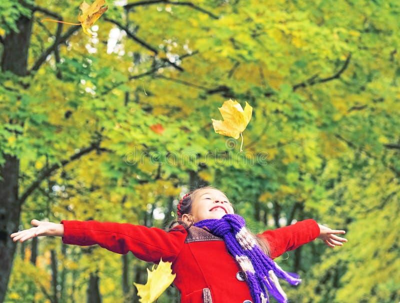 Λίγο γελώντας όμορφο κορίτσι στο κόκκινο παλτό ρίχνει τα κίτρινα φύλλα στο πάρκο φθινοπώρου στοκ φωτογραφίες