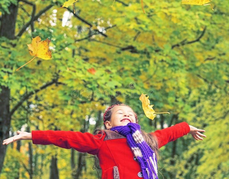 Λίγο γελώντας όμορφο κορίτσι στο κόκκινο παλτό ρίχνει τα κίτρινα φύλλα στο πάρκο φθινοπώρου στοκ εικόνα με δικαίωμα ελεύθερης χρήσης