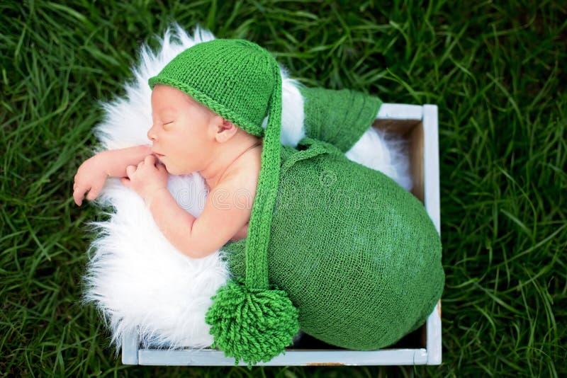 Λίγο γλυκό νεογέννητο αγοράκι, που κοιμάται στο κλουβί με το περικάλυμμα και το χ στοκ εικόνα με δικαίωμα ελεύθερης χρήσης