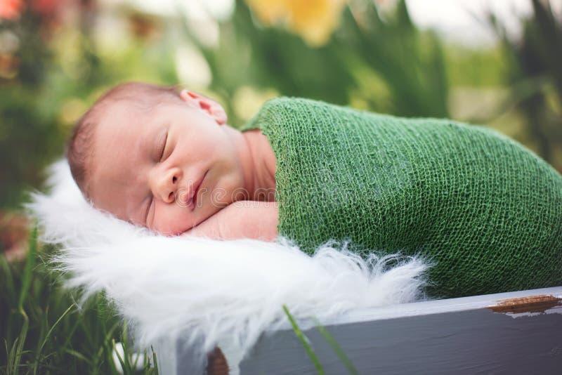 Λίγο γλυκό νεογέννητο αγοράκι, που κοιμάται στο κλουβί με το περικάλυμμα και το χ στοκ φωτογραφία με δικαίωμα ελεύθερης χρήσης
