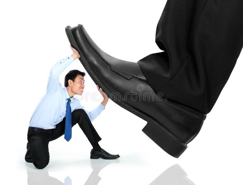 Λίγο επιχειρησιακό άτομο που συντρίβεται από τα πόδια στοκ φωτογραφίες με δικαίωμα ελεύθερης χρήσης