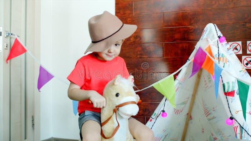 Λίγο ευτυχές αγόρι που φορά το καπέλο κάουμποϋ οδηγά ένα άλογο παιχνιδιών στο χώρο για παιχνίδη στοκ εικόνες