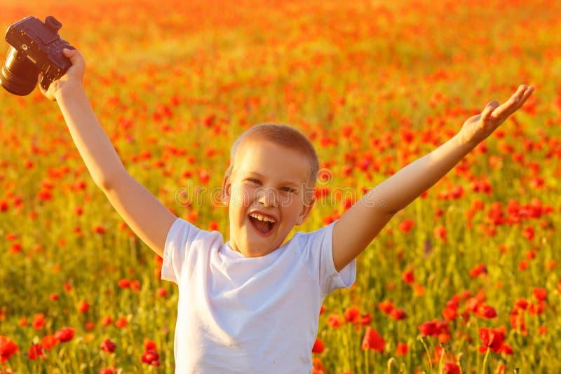 Λίγο ευτυχές αγόρι στον τομέα παπαρουνών στο ηλιοβασίλεμα με τη κάμερα στοκ φωτογραφία