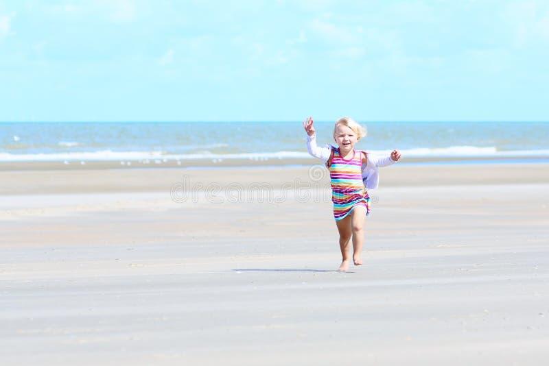 Λίγο ευτυχές κορίτσι που παίζει στην παραλία στοκ εικόνα με δικαίωμα ελεύθερης χρήσης