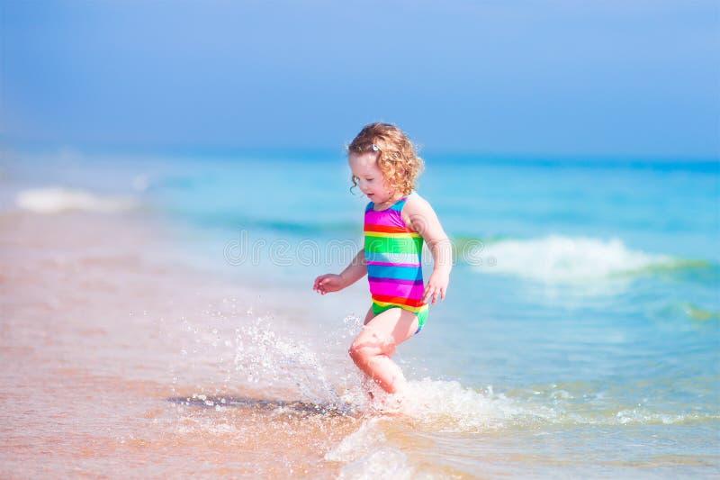 Λίγο ευτυχές κορίτσι που τρέχει σε μια παραλία στοκ φωτογραφίες
