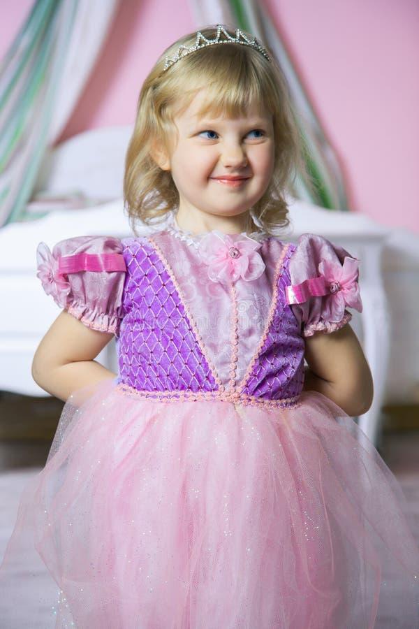 Λίγο ευτυχές κορίτσι πριγκηπισσών στο ρόδινο φόρεμα και κορώνα στο βασιλικό δωμάτιό της που θέτει και που χαμογελά στοκ φωτογραφία