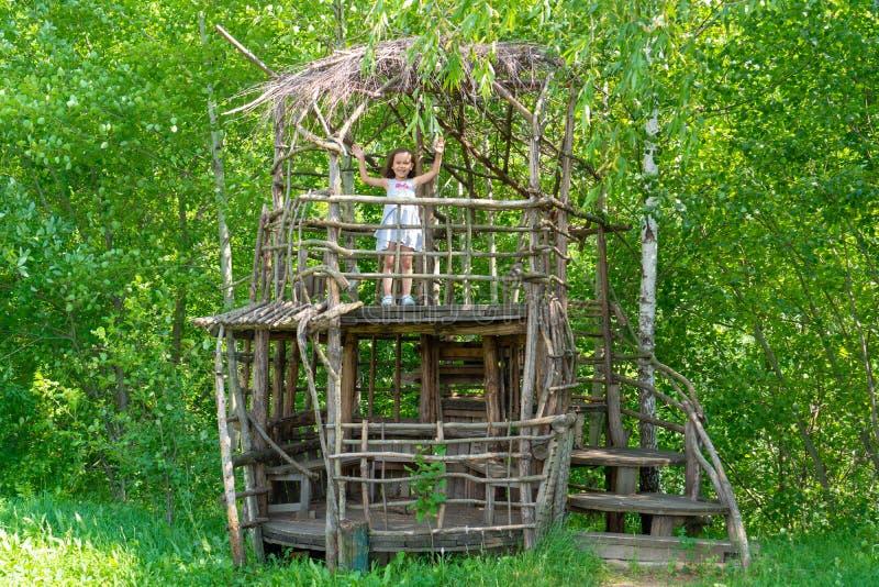 Λίγο ευτυχές κορίτσι σε ένα ξύλινο σπίτι δέντρων μια ηλιόλουστη ημέρα Το παιδί χαίρεται το καλοκαίρι r στοκ φωτογραφίες