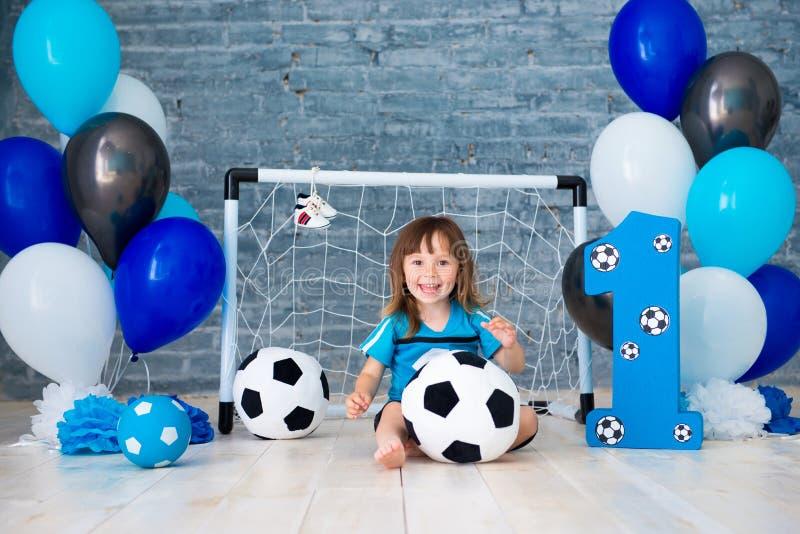 Λίγο εύθυμο παιδί έντυσε στα αθλητικά ενδύματα καθμένος στο πάτωμα κοντά σε έναν στόχο ποδοσφαίρου, εξετάζοντας μια μεγάλη σφαίρα στοκ εικόνα με δικαίωμα ελεύθερης χρήσης